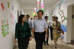 李雪梅校长(左一)带领国务院侨办谭副主任(前排右一)一行参观幼儿园环境
